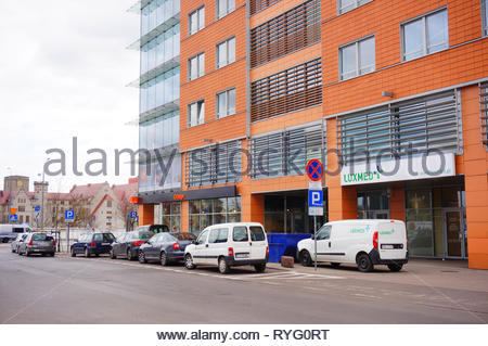 Poznan, Poland - March 8, 2019: Row of cars parked in front of a Luxmed medical office and a Orange salon in the Globis building on the Slowackiego st - Stock Photo