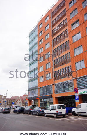 Poznan, Poland - March 8, 2019: Row of parked cars in front of a Luxmed medical office and Orange shop in the Globis office building on the Slowackieg - Stock Photo
