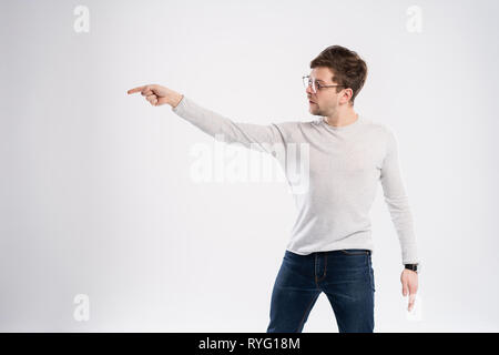 Happy smiling young man presenting and showing your text or product isolated on white background. - Stock Photo
