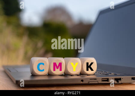 Symbol for the CMYK color model. Dice placed on a notebook with the letters 'CMYK' with corresponding colors. - Stock Photo