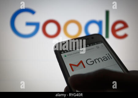 Gmail, free email service developed by Google. Logo on its website is seen on a smartphone display, Google logo unfocused on background - Stock Photo