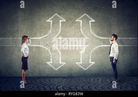 Confident businesswoman and businessman looking into the future as a crossroad arrows split in three different ways finding a common way. - Stock Photo