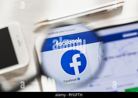 California, USA - 7 March 2019: Facebook, social network official website homepage under magnifying glass. Concept Facebook, social network logo - Stock Photo