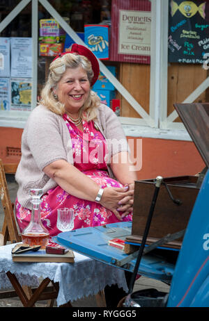 Woodhall Spa 1940s Festival - woman dressed in 1940s outfit sat at the street party - Stock Photo