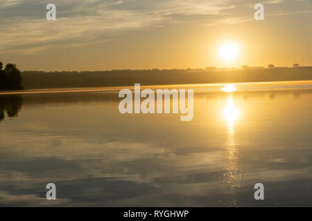 Landscape of early spring at morning sunrise on river. Bright sun lights through trees on horizon. Beautiful spring nature - Stock Photo