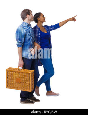 Back view of interracial going couple with a picnic bag who points somewhere. Two students go to the lecture. Rear view people collection. backside vi - Stock Photo