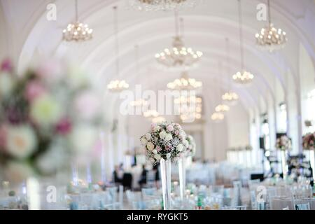Big wedding hall well decorated in pastel colors with chandeliers on vaulting. - Stock Photo