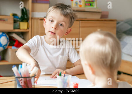 Young boy painting in his bedroom - Stock Photo