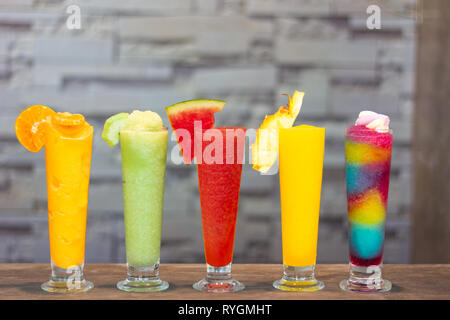 Colorful fresh smoothies with Tropical Fruits on grey background, healthy detox or diet concept - Stock Photo