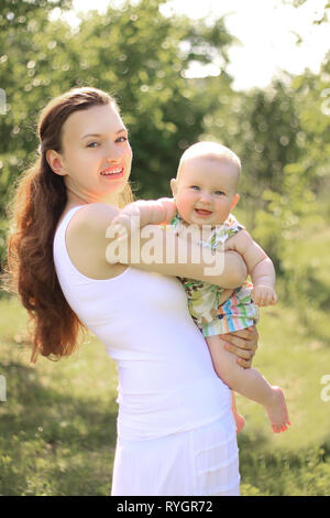 smiling mother and happy one-year-old daughter on a walk in the Park - Stock Photo