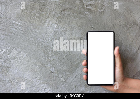 Asian woman hand hold moblie phone on grey cement background - Stock Photo