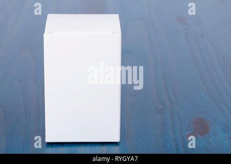 A white cardboard box on wooden background painted blue. - Stock Photo