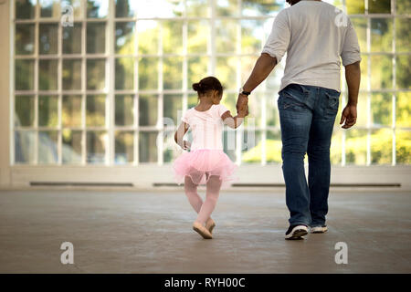 Mid adult man holding the hand of his young daughter. - Stock Photo