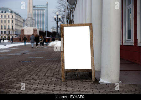Blank ad space on a wooden stand in the street outside - Stock Photo