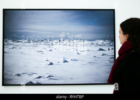 Saatchi Gallery, London, UK 14 Mar 2019 - A woman views a photograph of Point Hope, Alaska USA, May 2018. Only a narrow stretch of ice is left where it used to be much wider, stretching into the ocean. In April 2018, sea ice area was only 13.7 km square, the lowest figure ever observed in April since the beginning of satellite observations.   Carmignac Photojournalism award - ÒArctic - New FrontierÓ exhibition by Yuri Kozyrev and Nadir Vab Lohuizen on show at Saatchi Gallery. Credit: Dinendra Haria/Alamy Live News - Stock Photo