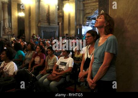 Rio De Janeiro, Brazil. 14th Mar, 2019. People attend a service in honour of the murdered city councillor Marielle Franco and her driver Anderson Gomes one year after her death. The politician of the left party PSOL was shot dead in her car on March 14, 2018. She was active against violence and corruption in the slums of Rio de Janeiro. She apparently turned the mighty militias against her. Credit: Ian Cheibub/dpa/Alamy Live News - Stock Photo