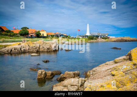 Rocky coast of Baltic Sea in Allinge, Bornholm, Denmark. Chimney of smokehouse in the background. - Stock Photo