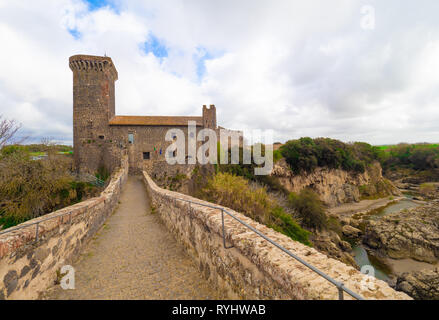 Vulci (Italy) - The medieval castle of Vulci, now museum, with Devil's bridge. Vulci is an etruscan ruins city in Lazio region, on the Fiora river - Stock Photo