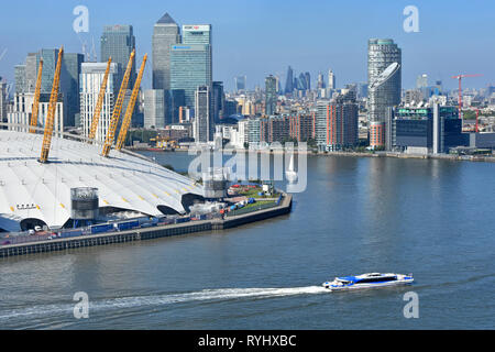 Aerial view looking down from above at bend in River Thames with clipper boat & London Canary Wharf cityscape skyline o2 arena dome roof Greenwich UK - Stock Photo