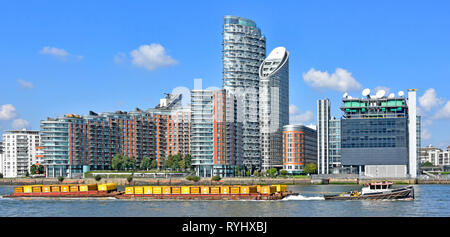 River Thames tug boat & barge containers full of London waste rubbish towed down river for recycling modern apartment building Poplar East London UK - Stock Photo