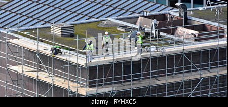 Aerial birds eye view from above London tall office building roof workers erecting access scaffolding for rooftop repairs City of London England UK - Stock Photo