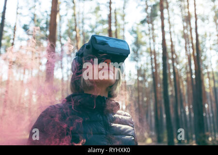 A woman wearing virtual reality goggles in the forest sees smoke bombs. VR glasses. - Stock Photo