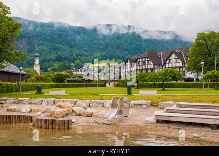 St. Gilgen, Austria - June 2, 2017: Beach on Wolfgangsee lake with woodens seats, children's playground, green lawn and a view of mountains. - Stock Photo
