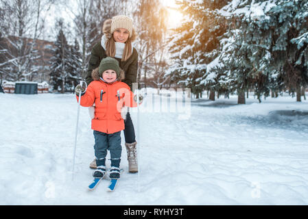 A young woman, mom supports with care, skiing in winter in the forest park, a little son a boy of 3-6 years. The first sports lessons on the street - Stock Photo
