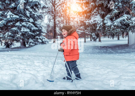 Little boy 3-5 years old, in the park in the winter walks on children's skis. Happy smiling plays, first steps in sport, free space for text. Emotions - Stock Photo