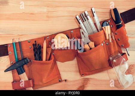 Organized handyman tool belt on work desk - Stock Photo