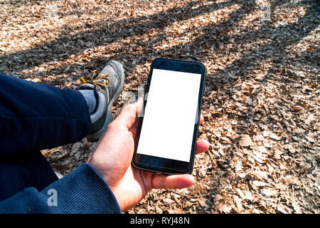 Mockup image of smart phone with white blank screen template, hand holding and showing mobile in nature outdoor. - Stock Photo