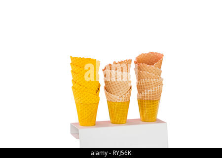 Ice cream cones made of baked wafers in the shape of cones with different color shades in plastic cups on a stand isolated on a white background. - Stock Photo