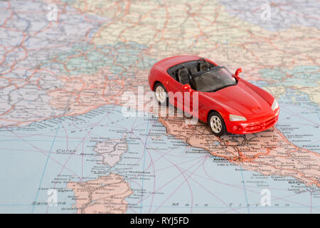 Toy red car on the geographical map of Europe. Travel route planning concept. - Stock Photo