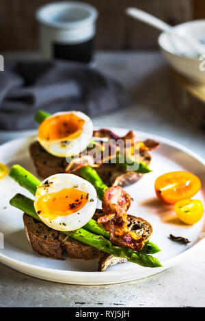 Bacon ,Seared Aspargus and Soft boiled egg  on Rye bread open Sandwich - Stock Photo