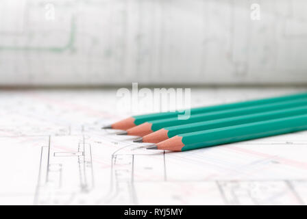 Architectural plans lying on drawing board with green pencils - Stock Photo
