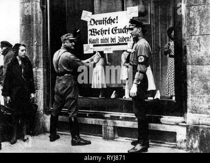 Nazism / National Socialism, persecution of the Jews, boycott of Jewish stores, storm battalion man and SS man sticking boycott poster on shop window, 'Deutsche! Wehrt Euch! Kauft nicht bei Juden!' probably Berlin, Germany, 1.4.1933, Additional-Rights-Clearance-Info-Not-Available - Stock Photo