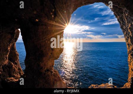 Romantic sundown seen through  a rock arch - Stock Photo