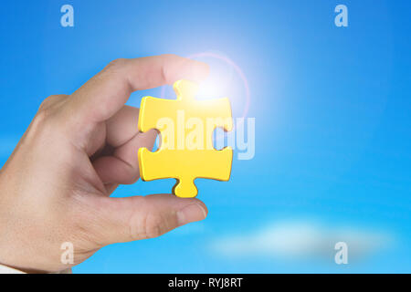 Hand holding gold jigsaw puzzle piece with blue sky sunlight background - Stock Photo
