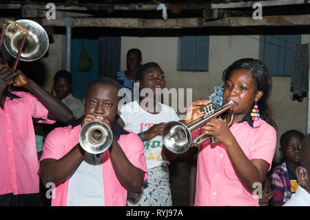 Anekro, ivory coast-August 20, 2015: Saxophonists with a young woman at a party service to the village - Stock Photo
