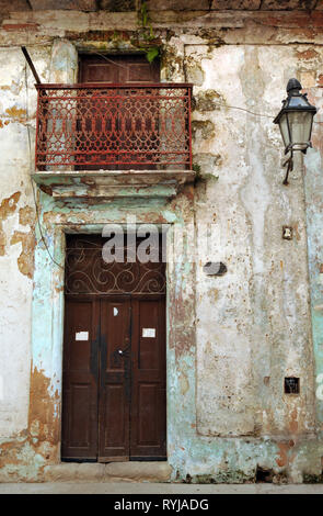 The front door and balcony of a dilapidated residential building in Old Havana, Cuba. Many of the city's historic buildings are in need of repair. - Stock Photo