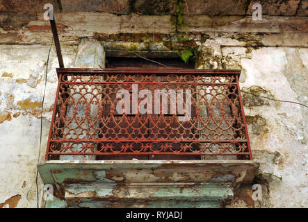 Detail of an ornate iron balcony on a dilapidated residential building in Old Havana, Cuba. - Stock Photo
