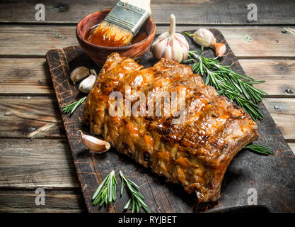 Grilled ribs with rosemary, spices and sauce. On a wooden background. - Stock Photo