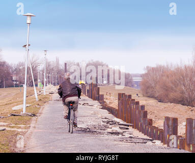 Man cycling on the flood protection dam during the construction work. - Stock Photo