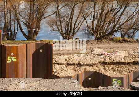 Steel pillar hitting in the ground to stabilizes the flood protection dam. - Stock Photo
