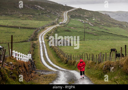 Dursey Island, Cork, Ireland. 18th June, 2016  A woman walks on the main road on a wet day in the townland of Kilmichael on Dursey Island, Co. Cork, I - Stock Photo