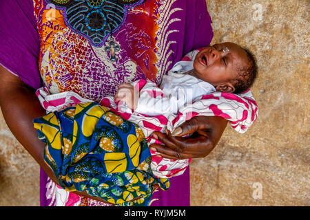 Mother holding baby near Agboville, Ivory Coast. - Stock Photo