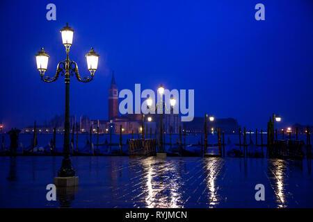 Italy, Veneto, Venice, the lights of a rainy night in Piazza Degli Schiavoni banks with the St. Giorgio abbey in the background - Stock Photo