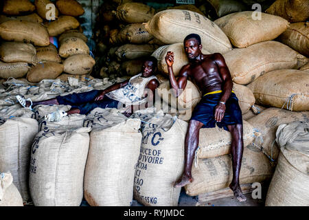 Cocoa workers resting in Agboville, Ivory Coast. - Stock Photo