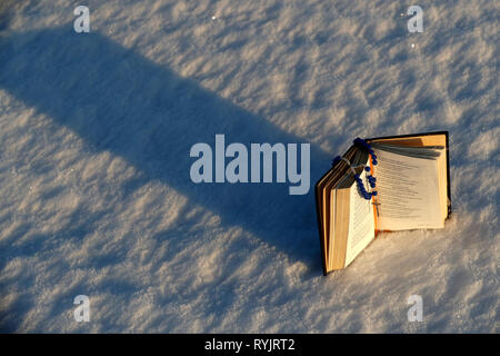 Book of common prayer and rosary on snow.  Norway. - Stock Photo