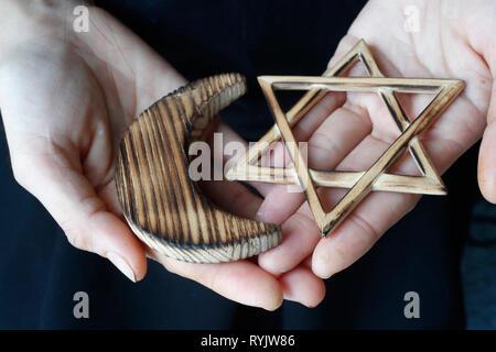 Islam and Judaism.  Jewish  Star of David and muslim Crescent :  Interreligious symbols in hands. - Stock Photo